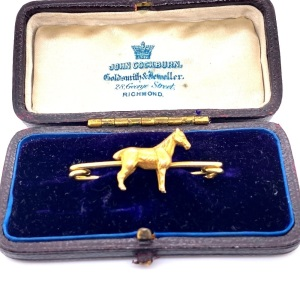 AN ANTIQUE HORSE BROOCH