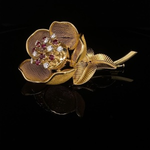 A VINTAGE FRENCH DIAMOND AND RUBY FLOWER BROOCH